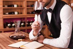 Sommelier examining wine. Cropped image of confident male sommelier examining wine while smelling it and leaning at the wooden table with wine shelf in the background