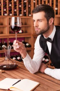This wine is perfect. Confident male sommelier examining wine while looking at the wineglass and leaning at the wooden table with wine shelf in the background